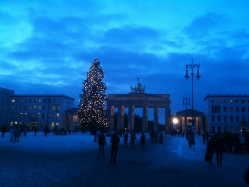 Brandenburg Gate just before nightfall, with a lighted Christmas tree and pedestrians walking by