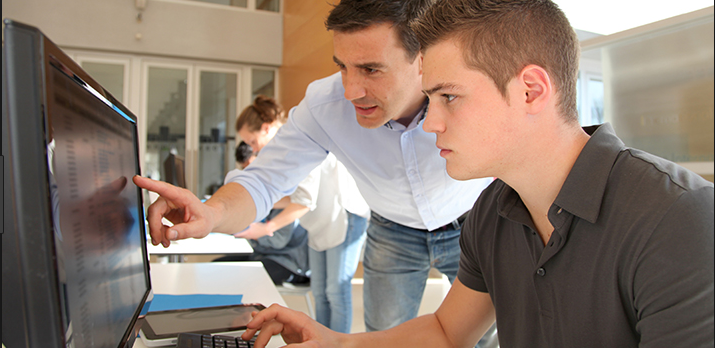 image of tutor helping student at computer
